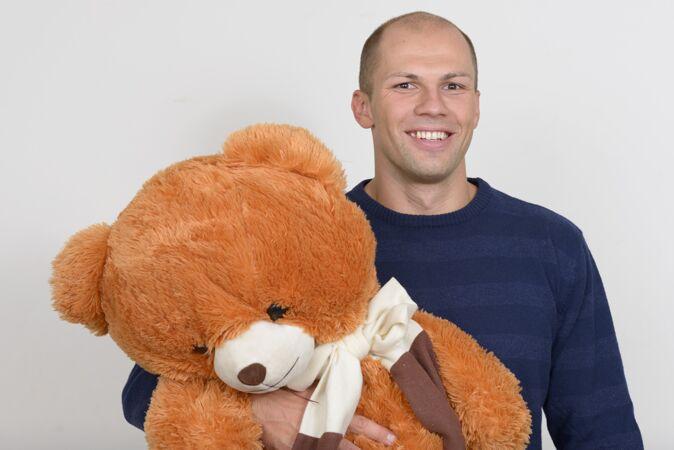 快乐的年轻英俊的秃头男子手持大泰迪熊的画像