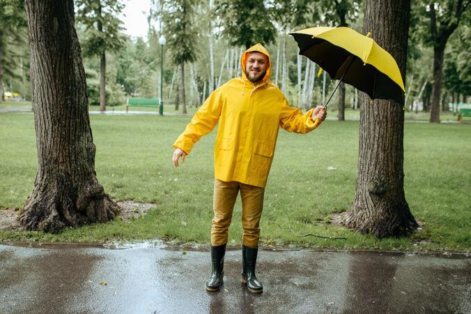 风雨交加的夏日公园里打着伞的男人白天男性穿着雨衣和胶靴的人 巷子里天气潮湿
