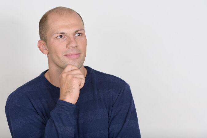 年轻帅气的秃头男人对着白色的空间
