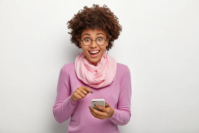 秀发清爽 面容姣好的女性 指着手机 戴上新的现代应用 表情愉快 戴着矫正视力的眼镜 紫色套头衫和丝巾