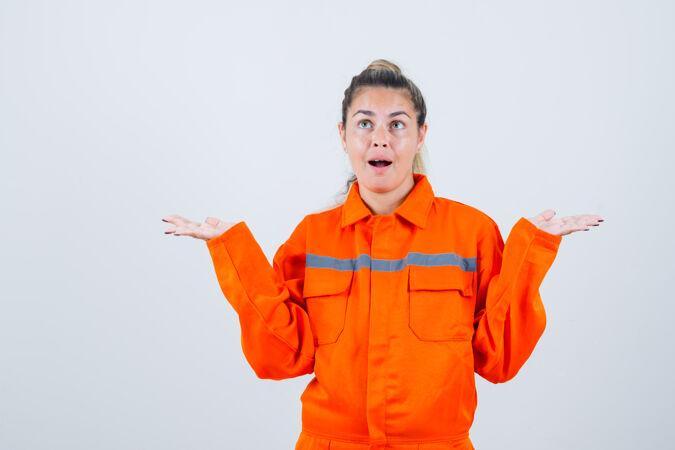 穿着工作服的年轻女性展示idk手势 看起来很困惑前视图