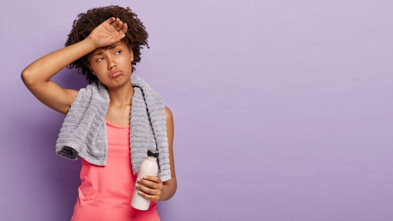 运动型的非洲裔女孩擦额头 满头大汗 穿着休闲背心 拿着装有淡水的瓶子 定期进行健身训练 肩上戴着毛巾