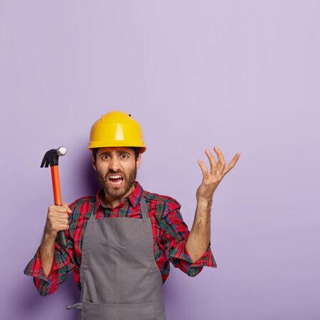 失意修理工的垂直镜头有着不解的表情 手里拿着锤子 义愤填膺地举起手臂 穿着工装 不懂修理什么