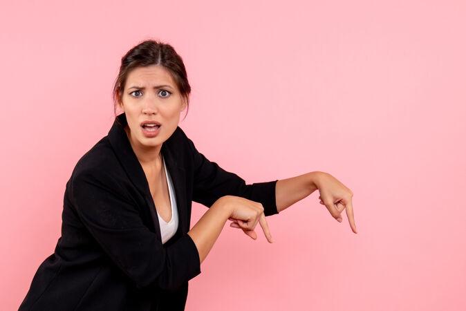 正面图年轻女性穿着粉色背景的深色夹克