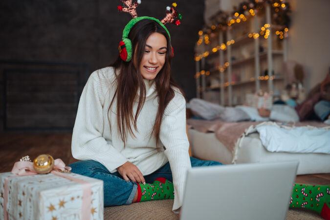 在家里庆祝圣诞节期间 一只雌性的鹿角微笑着用笔记本电脑和网友聊天