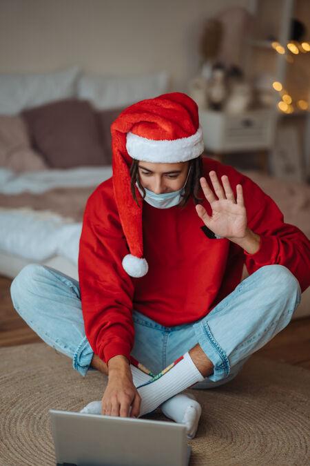 在笔记本电脑旁戴着圣诞帽的家伙正在通过视频通话进行互动在家里过圣诞节是一种与世隔绝的生活在假期里是一种社交距离