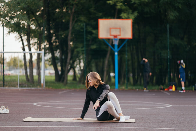 穿着运动服的年轻女子在户外的操场上训练